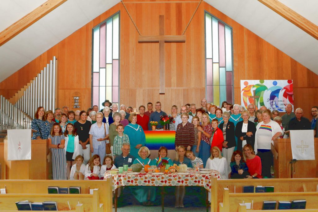 Photo of some of the LUMC Congregation gathered around thee communion table, in fall 2019.